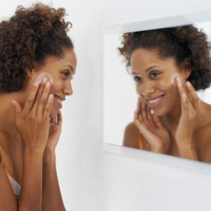 black-woman-looking-in-mirror-face-cream